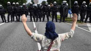 "A demonstrator holds her hands up as she faces policemen during a protest on July 7, 2017 in Hamburg, northern Germany, where leaders of the world""s top economies gather for a G20 summit"