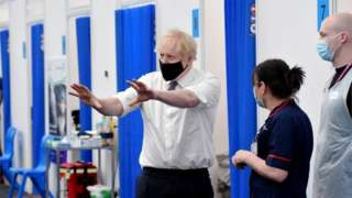 """Britain""""s Prime Minister Boris Johnson gestures as he visits a coronavirus disease (COVID-19) vaccination site at the Business Design Centre in Islington, London, Britain, May 18, 2021"""