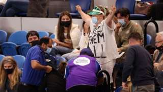 Security remove protesters from the crowd during the Australian Open final