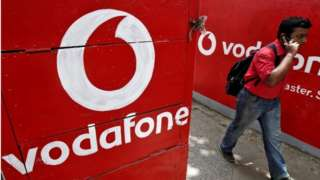 A man speaks on his mobile phone as he walks past logos of Vodafone painted on a roadside wall in Kolkata May 20, 2014