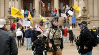 "People take part in a protest for ""Michiganders Against Excessive Quarantine"" at the Michigan State Capitol in Lansing, Michigan on April 15, 2020"