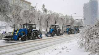 Utility service tractors clear snow after a snow storm in Vladivostok