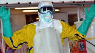 A health worker wearing protective gear is sprayed with disinfectant at the Nongo Ebola treatment centre in Conakry, Guinea, on August 21, 2015