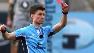 Referee Craig Maxwell-Keys shows a red card
