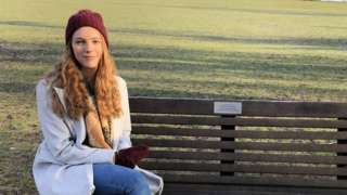 University student Emily Hutchinson sitting on one of the memorial benches she has written about in her e-book