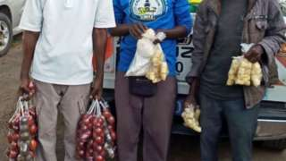 three vendors holding foodstuff in plastic bags