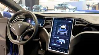 The interior on a Tesla Model S full electric luxury car with a large touch screen and dashboard screen.