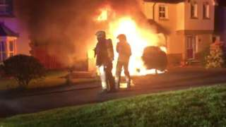 Firefighters tackling car fire