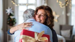 Portrait of senior couple with Christmas present indoors, hugging. - stock photo