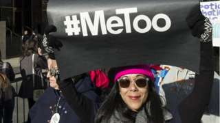 """A demonstrator holds up a banner saying """"#MeToo"""" in front of Trump International Hotel and Tower during the second annual Women's March in the borough of Manhattan in New York City"""