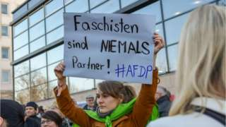"""People demonstrate outside Thuringia""""s State parliament building with a banner reading """"Fascists are never partners !"""""""