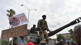 Zimbabwean Defence Force soldiers stand on a tank as they move forward through a crowd of people during a march in the streets of Harare.
