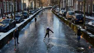 People skate on a frozen canal in a residential area of the Netherlands