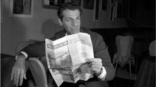 Sahl hodling a newspaper on stage