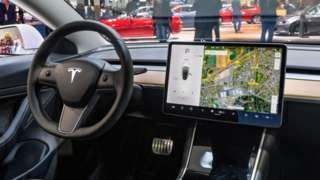 The interior of the Tesla Model 3, shown with a large tablet-like device mounted in the central console to the side of the steering wheel