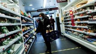 Woman in mask examines produce on shelves
