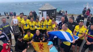 Veterans holding flags and celebrating at Land's end