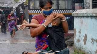 Una mujer corre debajo de la lluvia con un niño en brazos en Calcuta.