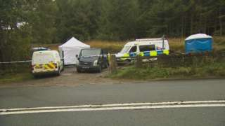 Police vehicles and forensic tents in the lay-by where the body was found