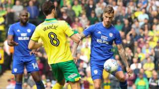 Joe Bennett of Cardiff City plays the ball past Mario Vrancic of Norwich City
