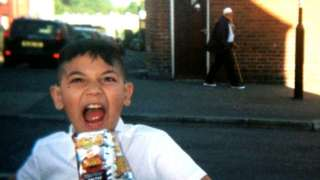 Young boy with bag of crisps (old man in background)