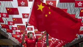 香港九龙尖沙咀东某购物商场外一位参与庆祝中共建党百年活动女士在挥舞中国国旗(29/6/2021)