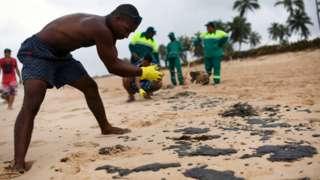 Homem limpando uma praia em Camaçari, Bahia
