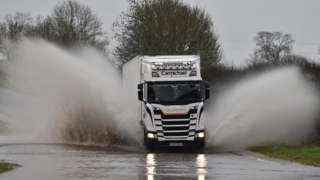 Lorry drives through flooded road