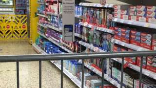 Railings cordoning off an area of Tesco containing sanitary products
