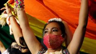 LGBT activists raise a rainbow flag during a protest in Bangkok, Thailand. Photo: 25 July 2020