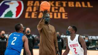 Basketball Africa League president Amadou Gallo Fall (centre) with the ceremonial tip off of the first game of the competition between Nigeria's Rivers Hoopers and Rwanda's Patriots