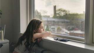A young girl stares out of a window on a rainy day, looking unhappy