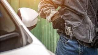 Foto de banco de imagens mostra homem tirando arma de bolso ao lado de um carro