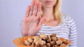 A woman refusing a bowl of peanuts