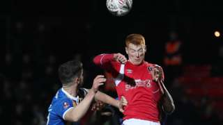 """Shrewsbury Town""""s Luke Waterfall (left) and Salford City""""s Rory Gaffney battle for the ball during the Emirates FA Cup"""