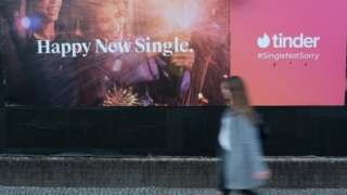 A young woman walks past a billboard advertisement for the dating app Tinder