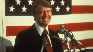 U.S. president Jimmy Carter smiling at a podium in front of an American flag, 1970s.