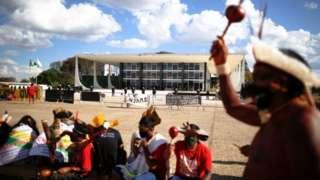 Indígenas em frente ao prédio do Supremo durante um dia, um deles levantando um objeto