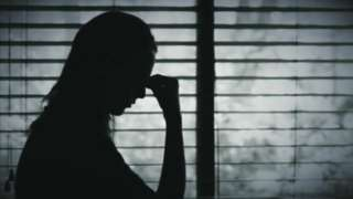 Woman in silhouette with fingers to head