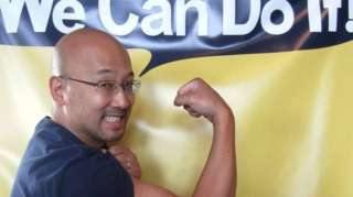 """Eugene Hung flexing his muscle under a banner saying """"We Can Do It!"""""""