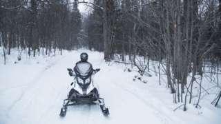 A woman riding a snowmobile