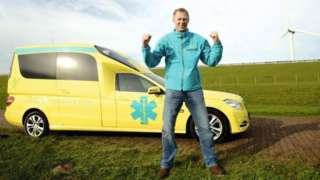 Kees Veldboer standing in front of his ambulance