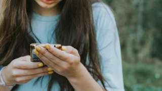 A girl using the cell phone outdoors - stock photo