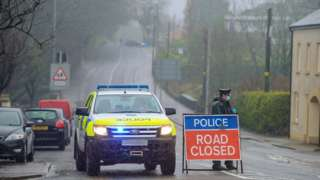 police at the scene of the alert with a road closed sign