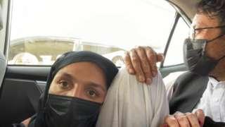 Zarifa Ghafari, usando um lenço que cobre o rosto, se esconde em um carro