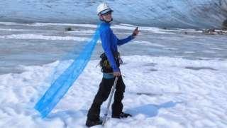 Celeste Labedz wearing a cape in front of a glacier
