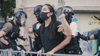 A young protester is detained by the police, after they caught up with her