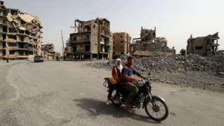 A couple on a moped amid the ruins of the Syrian city of Raqqa in October 2018