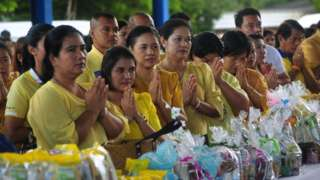 Well-wishers pray with offerings for Buddhist monks during a nationwide ceremony marking the birthday of the late Thai King Bhumibol Adulyadej in Thailand's southern province of Narathiwat on December 5, 2018.