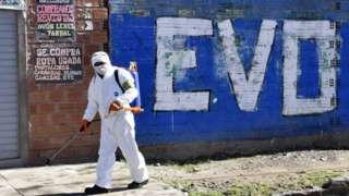 Trabajador de limpieza desinfectando una calle delante de una pinta de Evo Morales.